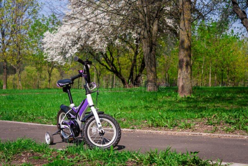 Bici blanco-púrpura de dos ruedas con las ruedas laterales adicionales foto de archivo libre de regalías
