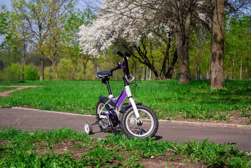 Bici blanco-púrpura de dos ruedas con las ruedas laterales adicionales fotos de archivo libres de regalías
