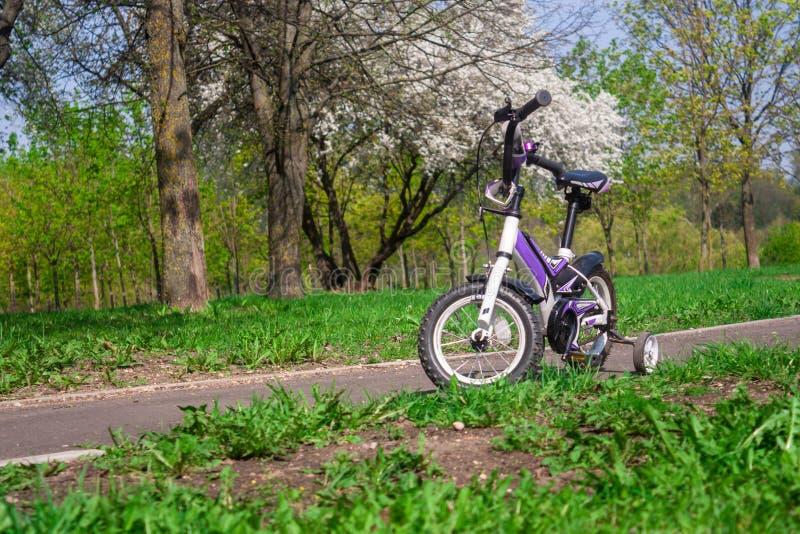 Bici blanco-púrpura de dos ruedas con las ruedas laterales adicionales foto de archivo