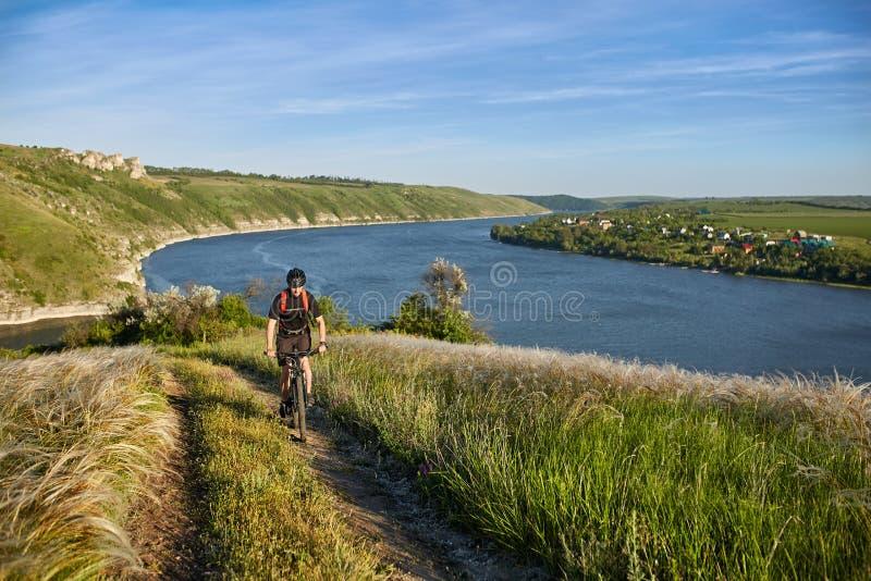 Bici de montaña joven del montar a caballo del ciclista cuesta arriba a lo largo de una carretera nacional sobre el río fotos de archivo libres de regalías