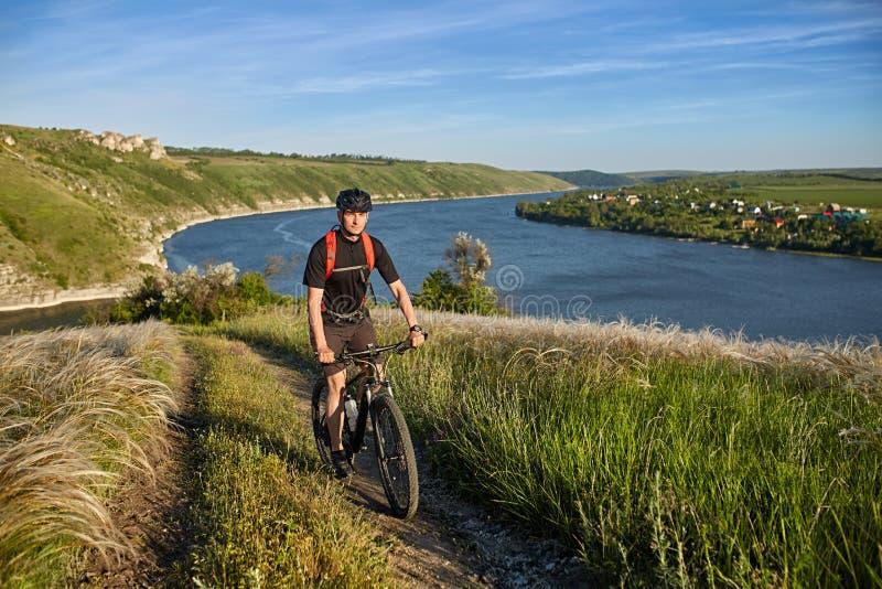 Bici de montaña joven del montar a caballo del ciclista cuesta arriba a lo largo de una carretera nacional sobre el río fotos de archivo