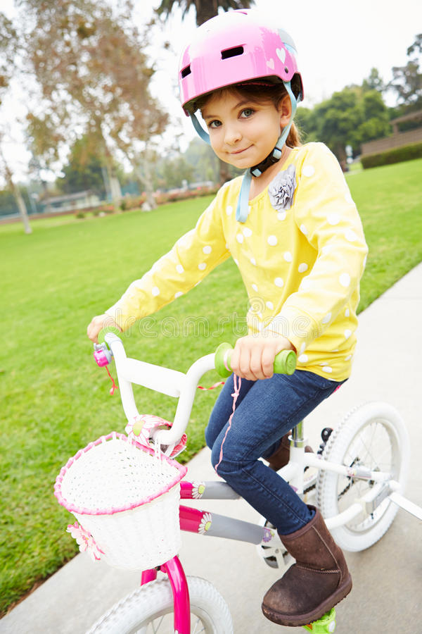 Bici del montar a caballo de la chica joven en parque foto de archivo libre de regalías