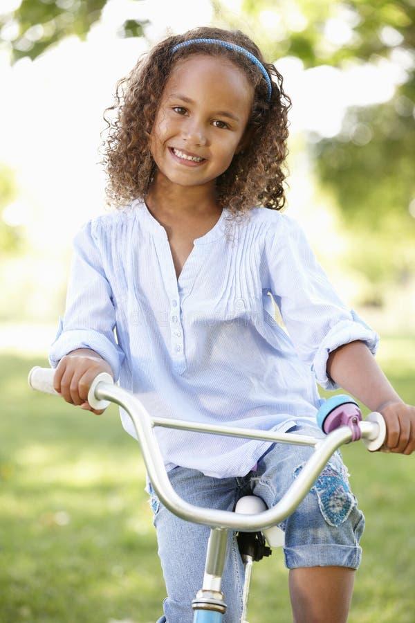 Bici del montar a caballo de la muchacha en parque imagen de archivo