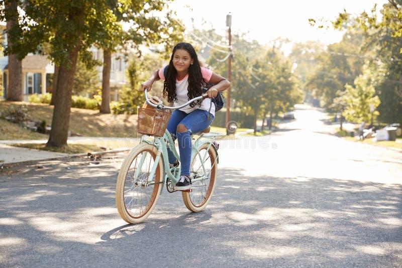 Bici del montar a caballo de la muchacha a lo largo de la calle a la escuela fotos de archivo