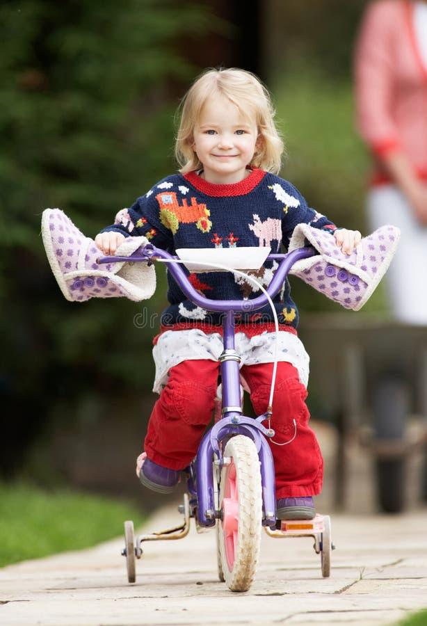 Bici del montar a caballo de la muchacha a lo largo de la trayectoria del jardín imagen de archivo