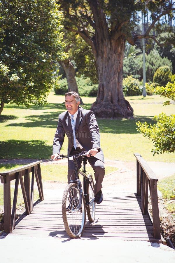 Bici del montar a caballo del hombre de negocios en el parque imagen de archivo