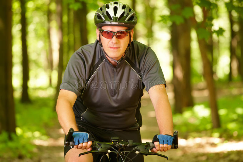 Bici del montar a caballo del hombre en bosque fotografía de archivo