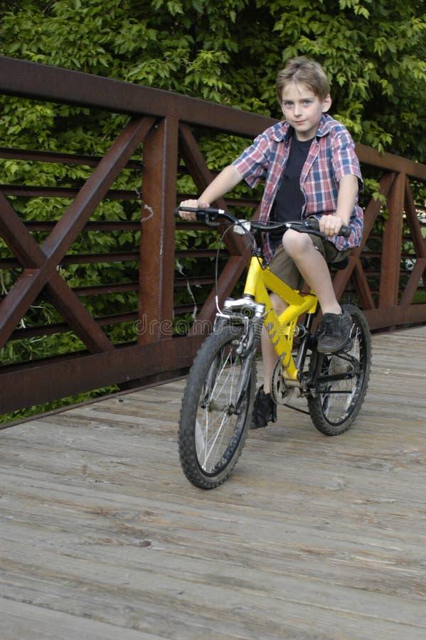 Bici del montar a caballo del muchacho en el puente imagen de archivo libre de regalías