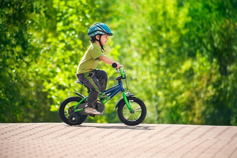 Bici del montar a caballo del muchacho en un casco fotografía de archivo