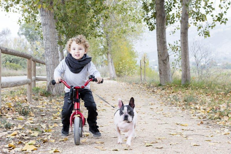 Bici del montar a caballo del niño con el perro imágenes de archivo libres de regalías
