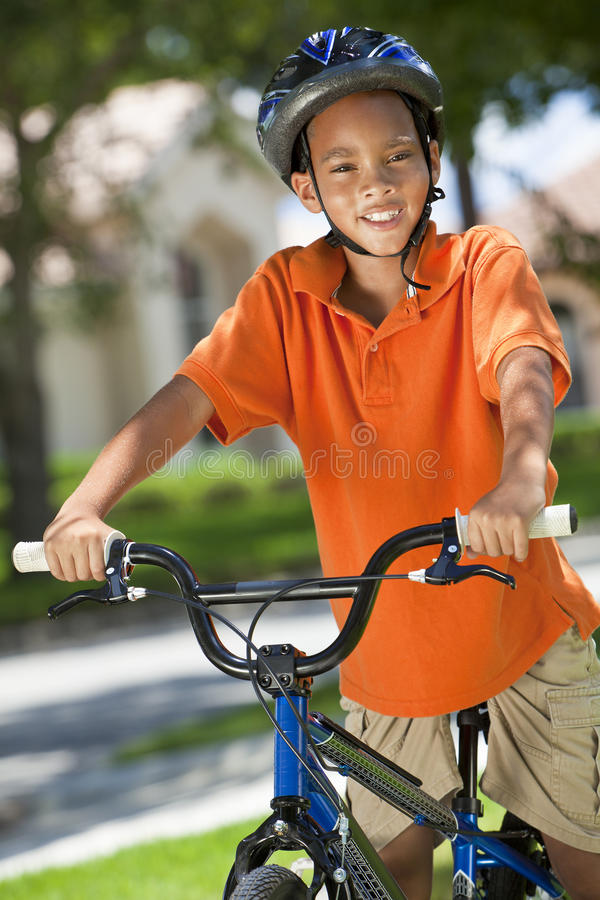 Bici del montar a caballo del niño del muchacho del afroamericano imagenes de archivo