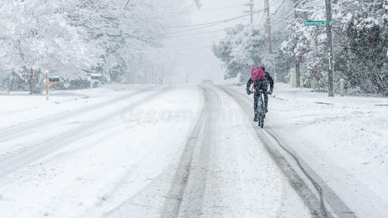 Bici del montar a caballo del hombre en la nieve foto de archivo