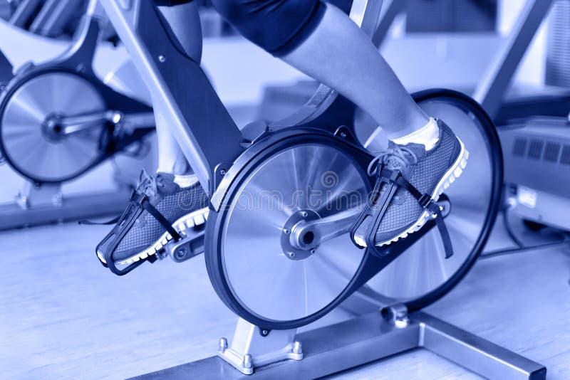 Bici di esercizio con le ruote di filatura - ciclismo della donna immagine stock