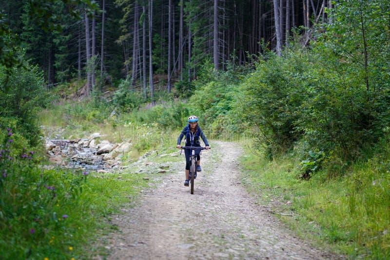 Bici di guida della giovane donna sulla strada della traccia della foresta fotografie stock libere da diritti
