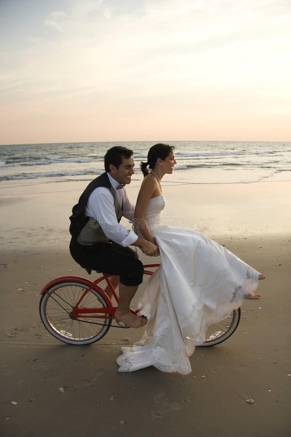 Bici di guida delle coppie sulla spiaggia fotografia stock libera da diritti