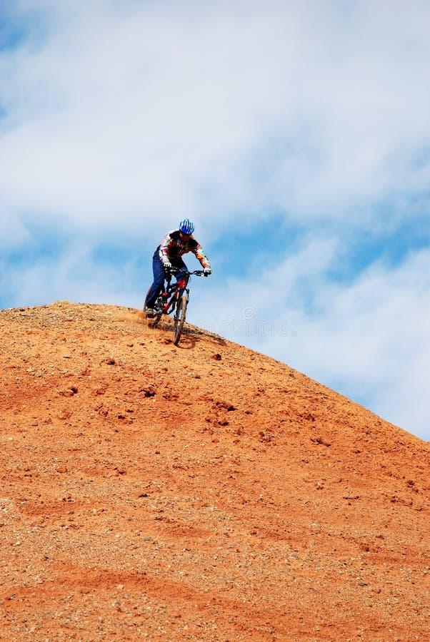 Bici in discesa sulla collina rossa immagini stock libere da diritti
