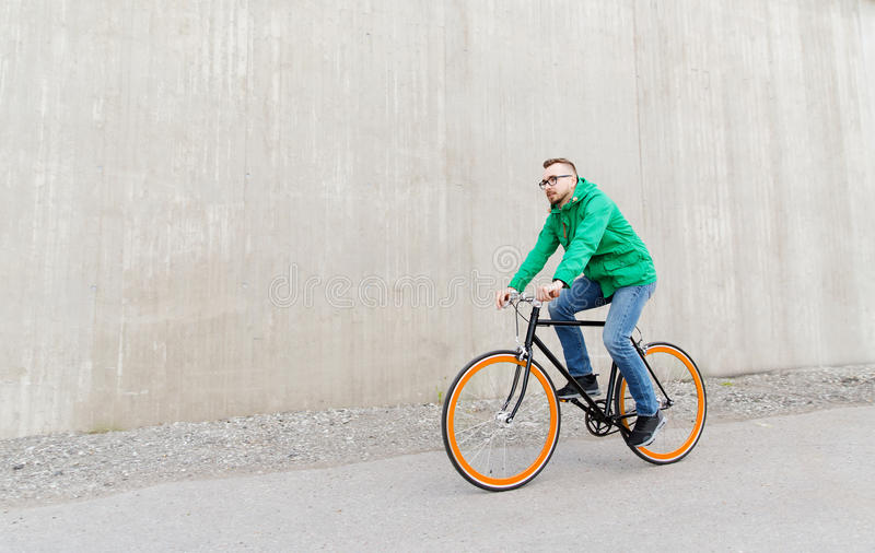 Bici fissa di guida dell'ingranaggio del giovane uomo felice dei pantaloni a vita bassa immagine stock libera da diritti