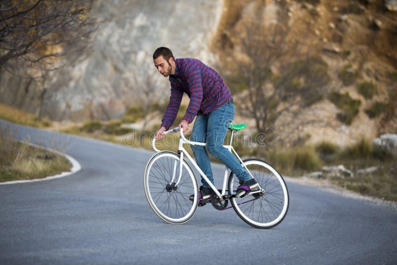 Bici fissa di guida di sport dell'ingranaggio dell'uomo del ciclista nel giorno soleggiato fotografie stock