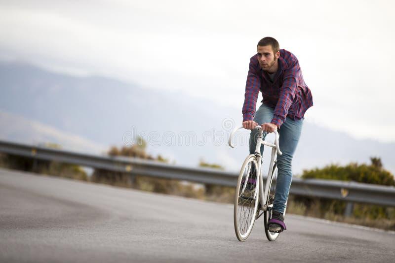 Bici fissa di guida di sport dell'ingranaggio dell'uomo del ciclista nel giorno soleggiato immagini stock