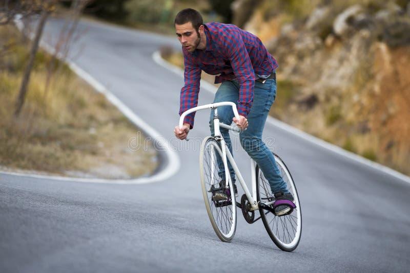 Bici fissa di guida di sport dell'ingranaggio dell'uomo del ciclista nel giorno soleggiato immagine stock libera da diritti