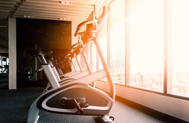 Bici fissa per l'esercizio nella stanza di forma fisica immagini stock libere da diritti