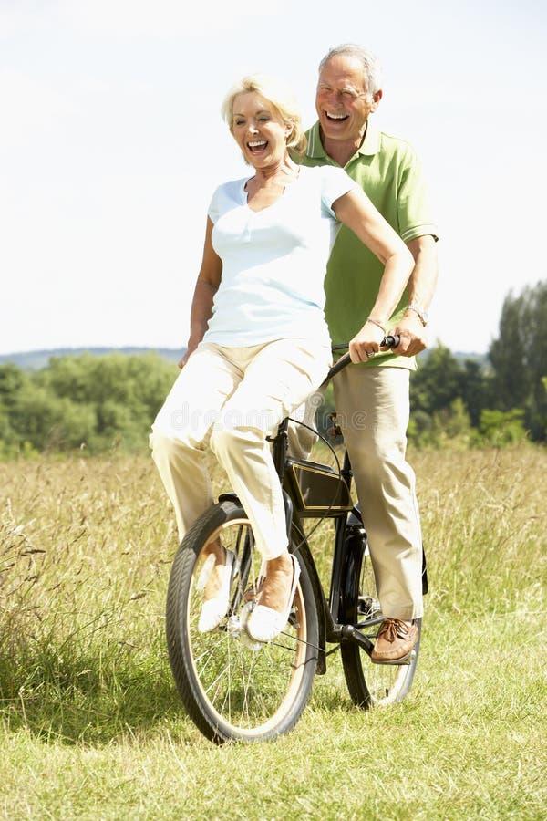 Bici madura del montar a caballo de los pares en campo