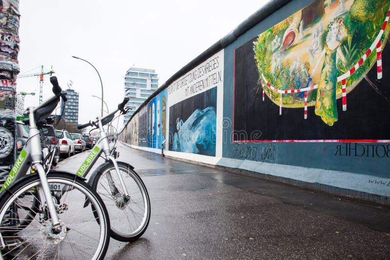 Bici pubbliche all'East Side Gallery del museo della parete su una conclusione fredda del giorno di inverno fotografia stock libera da diritti