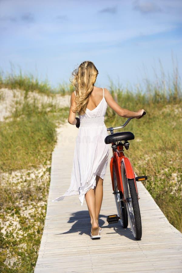 Bici que recorre de la muchacha en paseo marítimo imagen de archivo