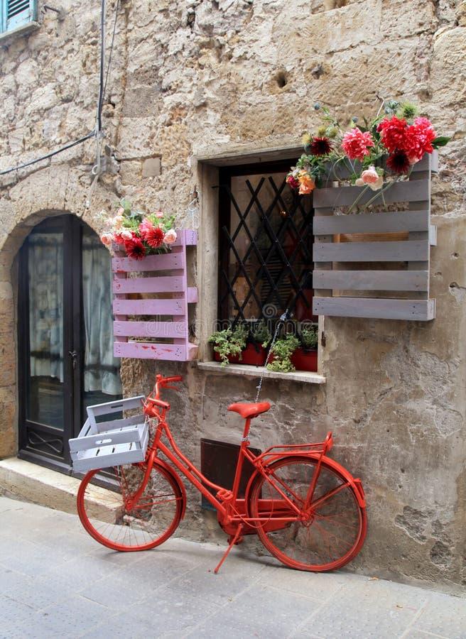 Bici roja en una ciudad medieval italiana tradicional, Toscana, Italia fotografía de archivo