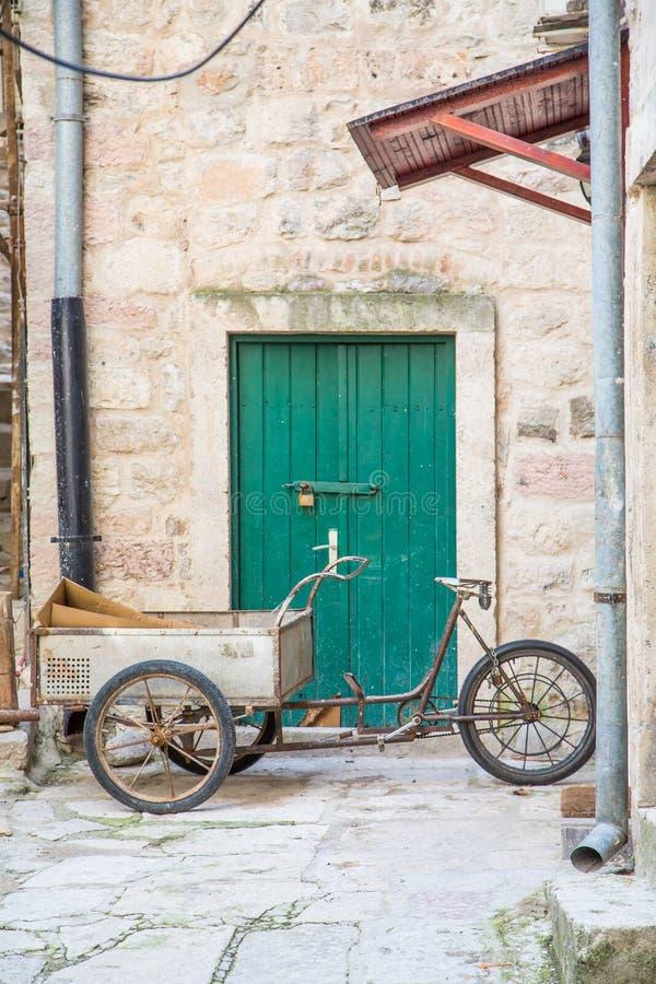 Bici a ruote tre con il carretto dalla porta verde immagine stock libera da diritti
