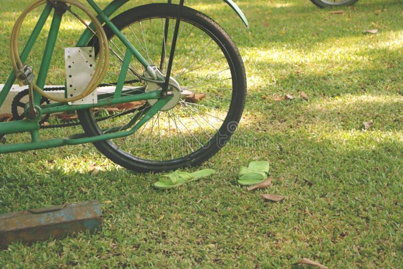 Bici verde d'annata su erba con l'accoppiamento delle scarpe di plastica fotografie stock
