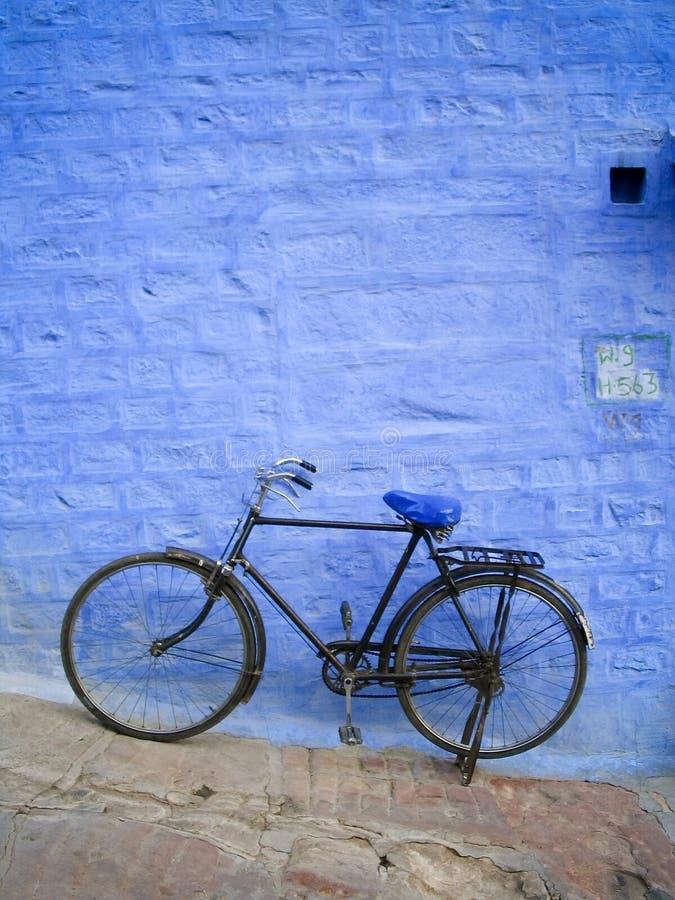 Bici vieja en la pared azul fotos de archivo
