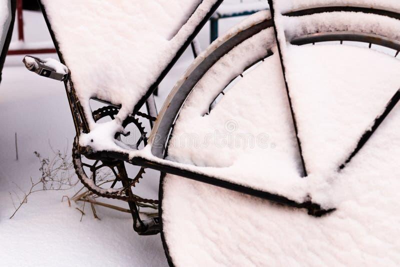 Bici vieja nevada en el aparcamiento de la bicicleta Invierno en las calles de la ciudad Tiempo Nevado fotografía de archivo