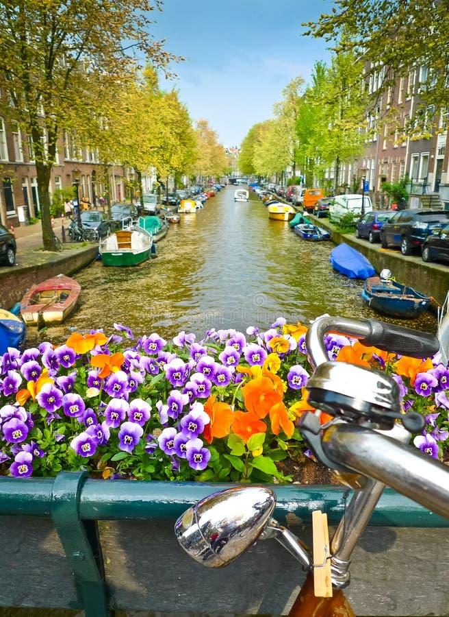 Bici y flores en un puente en Amsterdam imagenes de archivo