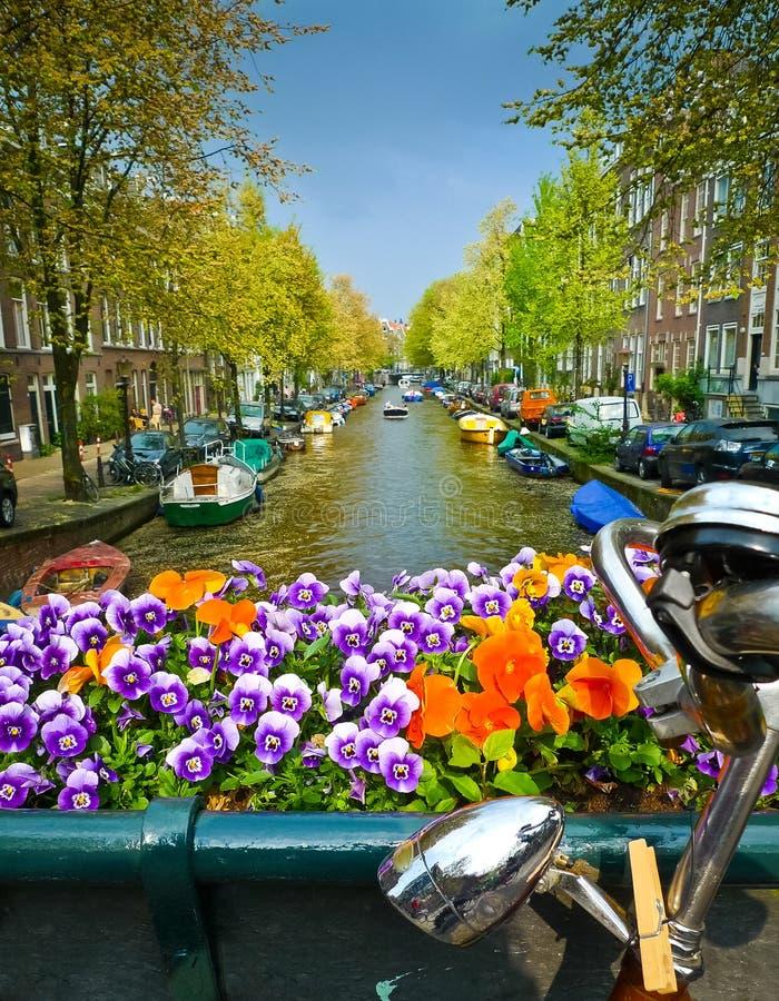 Bici y flores en un puente en Amsterdam fotografía de archivo