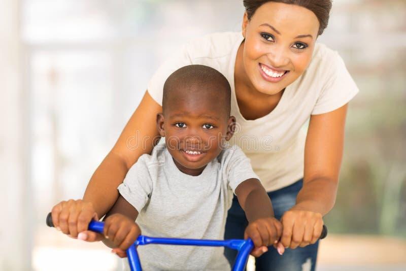 Bicicleta africana do filho da mãe fotografia de stock royalty free