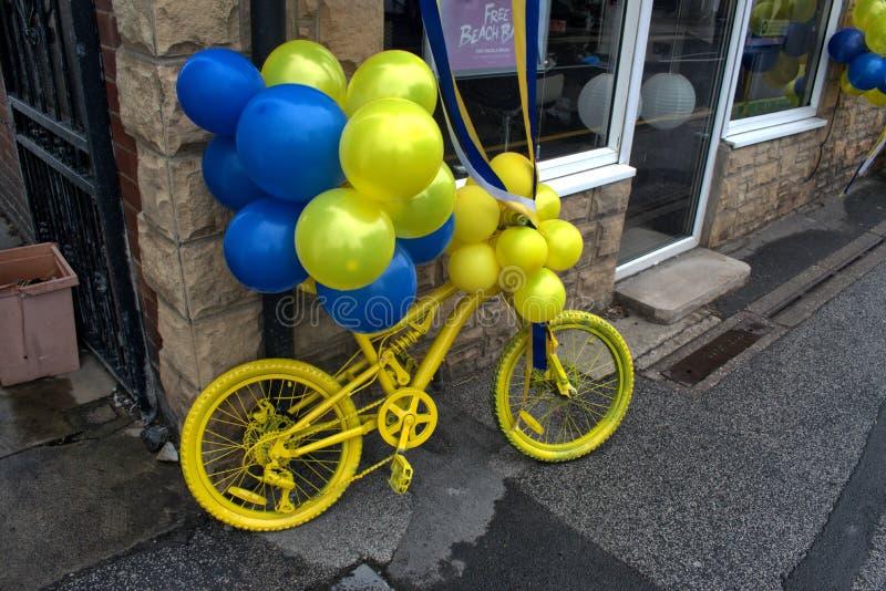 Bicicleta amarela, com os balões azuis e amarelos fotos de stock