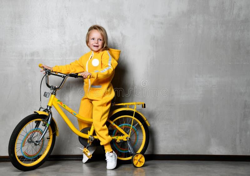 Bicicleta amarela do passeio da criança da moça primeira com para as rodas que olham o canto fotos de stock