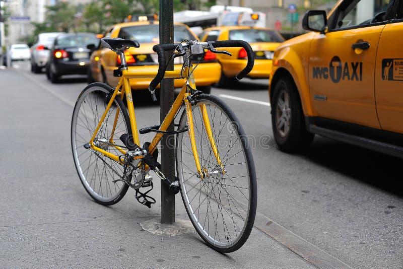 Bicicleta amarela e táxis amarelos imagens de stock royalty free