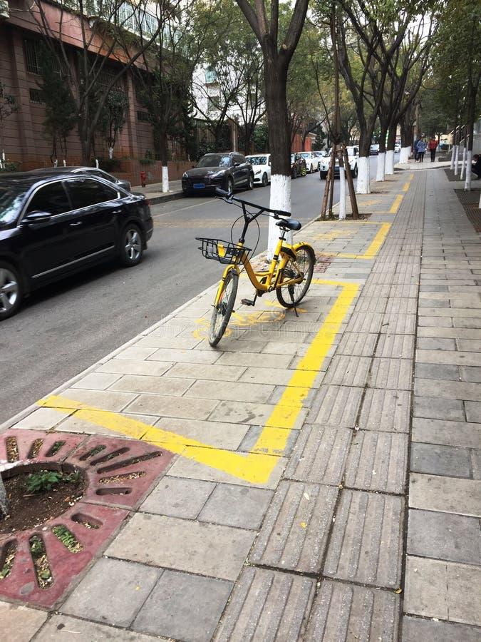 bicicleta amarela no estacionamento - bicicleta alugado fotos de stock royalty free