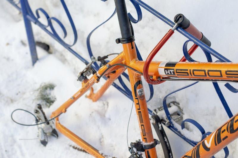 Bicicleta anaranjada Wheelless atada con correa a la cerca del hierro imagen de archivo