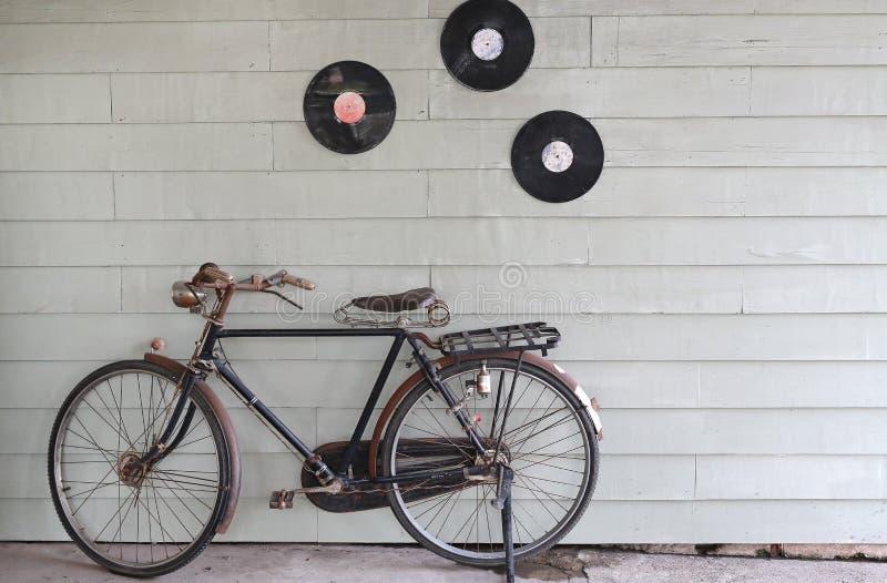 Bicicleta antigua vieja en el fondo de una pared de madera gris fotos de archivo