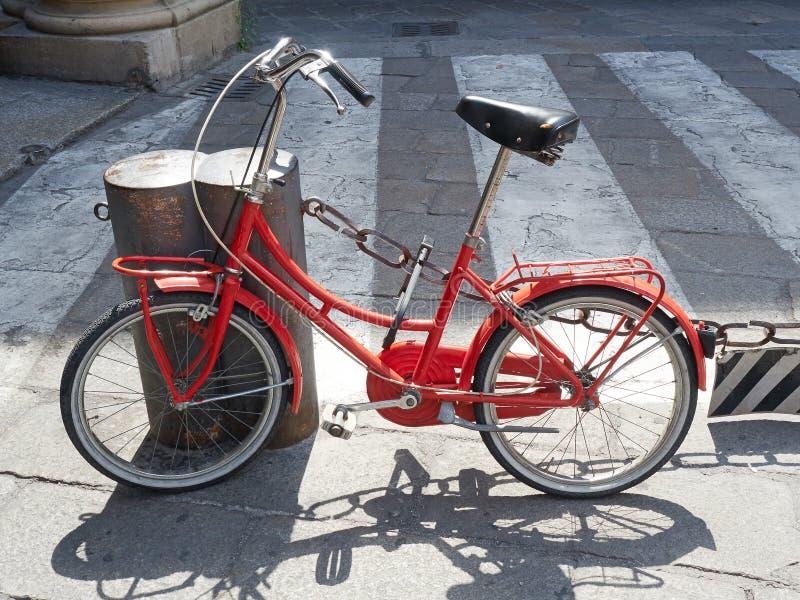 Bicicleta antiquado vermelha rua estacionada imagens de stock royalty free