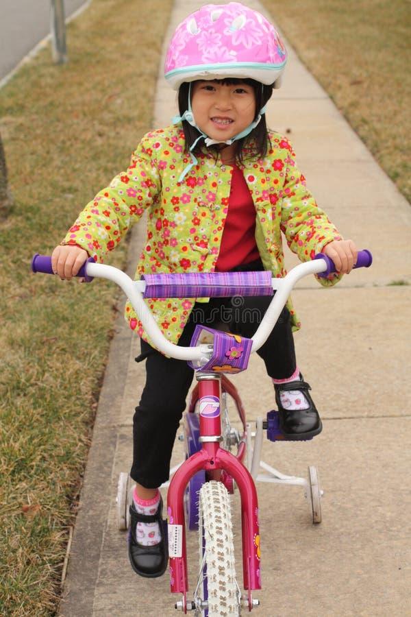 Bicicleta asiática da equitação da menina fotografia de stock