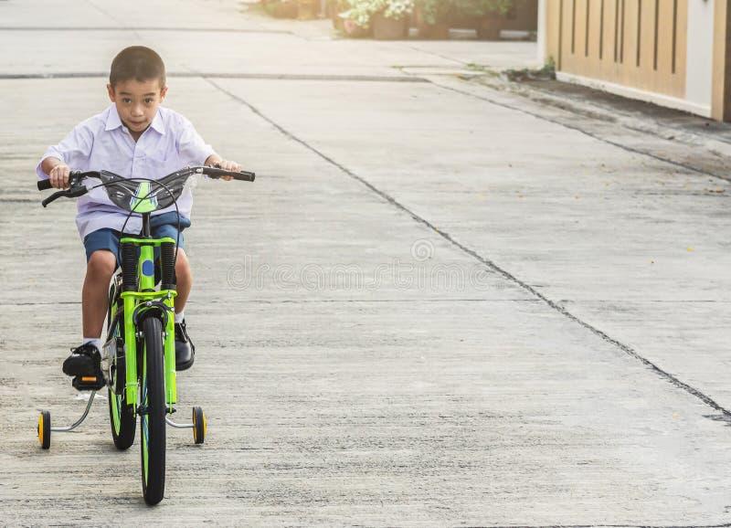 A bicicleta asiática do exercício dos estudantes da criança exterior na frente da vila para o treinamento biking do passeio feliz imagem de stock royalty free