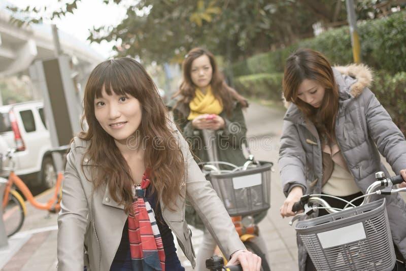 Bicicleta asiática joven del montar a caballo de la mujer con los amigos imagen de archivo