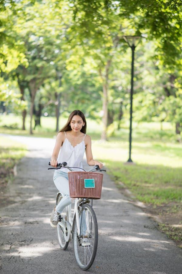 Bicicleta asiática moreno do passeio da menina no parque fotografia de stock royalty free