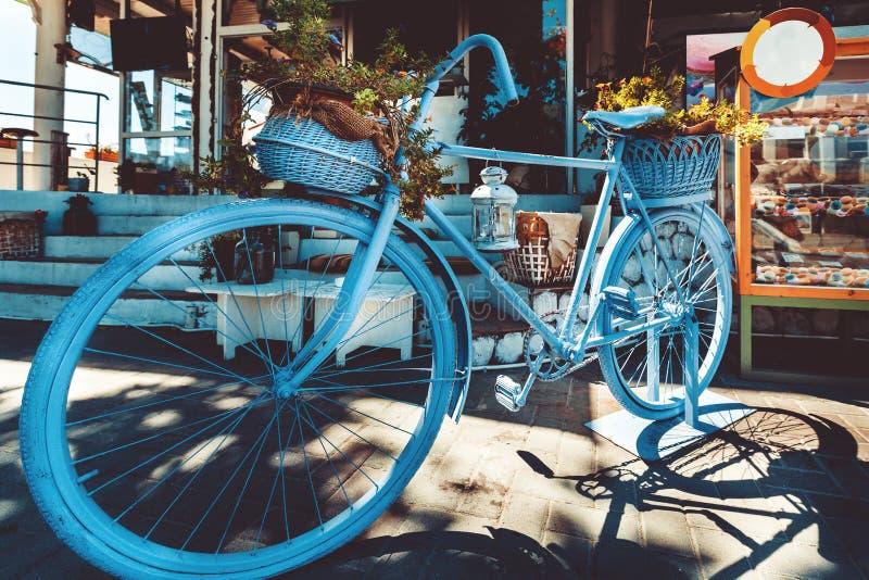 Bicicleta azul do vintage retro com a cesta das flores na rua de pedrinha foto de stock