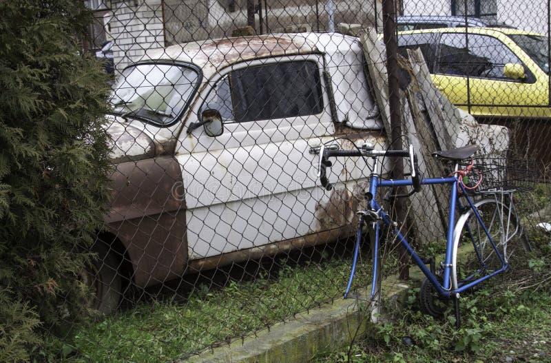 Bicicleta azul onde as rodas são removidas e um carro oxidado velho atrás de uma cerca fotos de stock