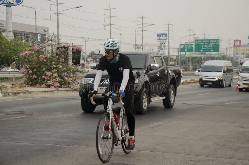Bicicleta biking asiática de la gente tailandesa en raza en la carretera de la calle con el camino del tráfico foto de archivo